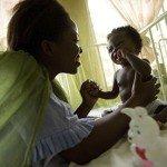 A woman attends her baby girl who sits under a mosquito net