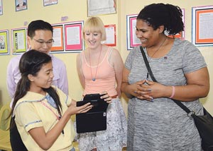 School visit in the Philippines; Filipina girl shows me and my colleagues her school work on a tablet